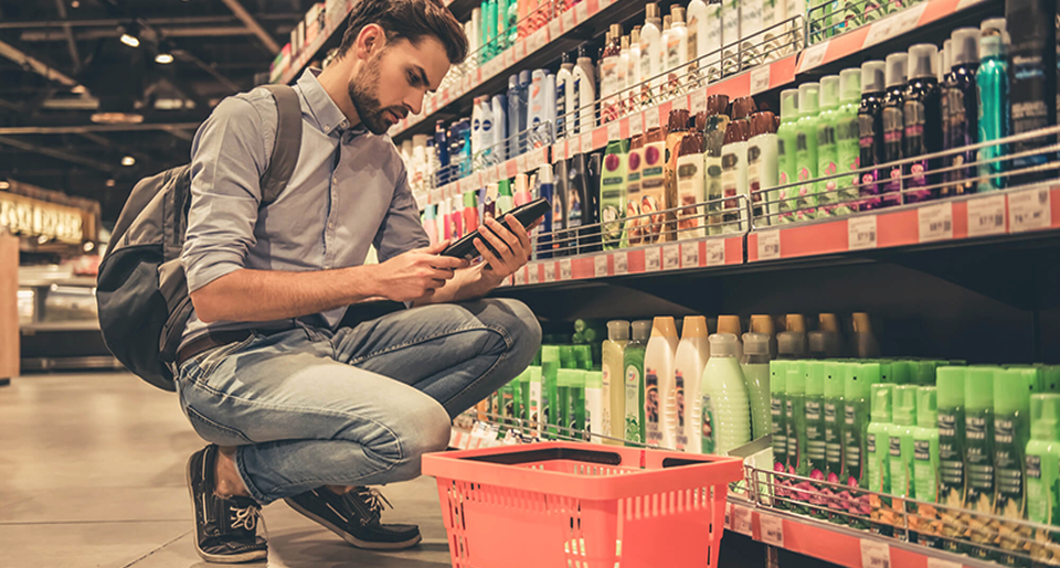 man looking at consumer product at a grocery store