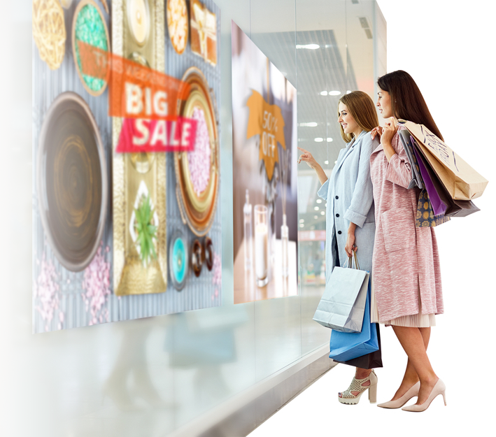 two girls looking at sales sign - signage