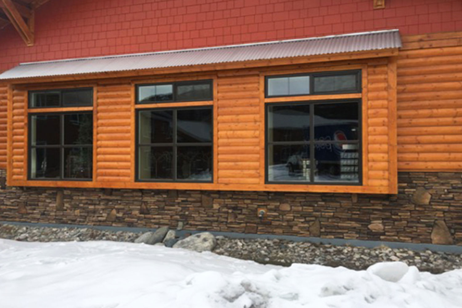 windows on the side of the house with logs