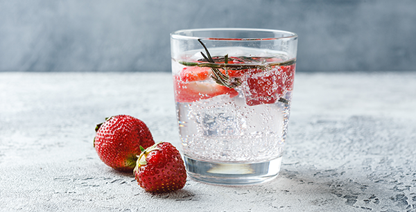 a glass of seltzer with strawberries