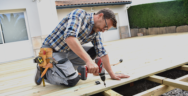 A man installing outdoor deck
